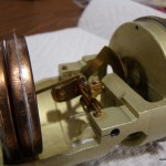 The aneroid wafer on the left as it contracts and expands moves the gear armature on the right